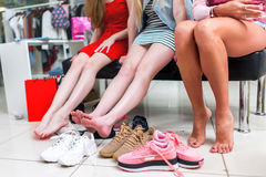 Close-up view of barefoot long slim female legs surrounded by variety of sports shoes. Three female friends sitting Stock Image