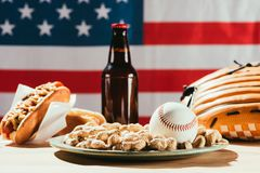close-up view of baseball ball on plate with peanuts and beer bottle with hot royalty free stock photography
