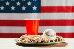 close-up view of baseball ball on plate with peanuts, red plastic bottle and american stock photos