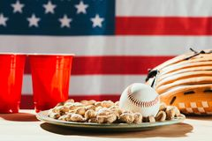 Close-up view of baseball ball on plate with peanuts, red plastic cups and baseball glove on table with us. Flag behind royalty free stock photography