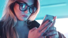 Close up view of beautiful blonde woman in eyeglasses and stylish leather surfing the internet. Social networks, modern stock video