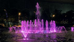 Close-up view of beautiful colorful fountain on city street at night. stock video footage
