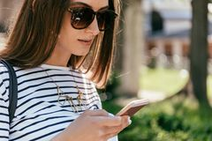 Close-up view of beautiful girl in sunglasses using smartphone. On street stock photography