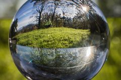 Close up view on beautiful landscape trees in blue sky and green meadow through lens ball sphere, france. Close up view on beautiful landscape trees in blue sky Stock Photo
