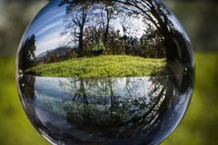 Close up view on beautiful landscape trees in blue sky and green meadow through lens ball sphere, france Stock Images
