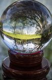 Close up view on beautiful landscape trees in blue sky and green meadow through lens ball sphere, france Royalty Free Stock Images