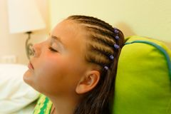 Close up view of a beautiful little girl napping, dreaming relaxing after stylish fashionable hair dreads was made. Head shot, close up view of a beautiful Stock Photography