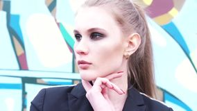 Close-up view of beautiful model with light brown hair, brown eyes and perfect stylish makeup posing near the wall with. Graffiti in a black jacket. Modern stock footage