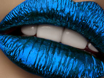 Close up view of beautiful woman lips with blue metallic lipstick. Open mouth with white teeth. Cosmetology, drugstore or fashion makeup concept. Beauty studio stock photography