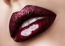 Close up view of beautiful woman lips. With dark red lipstick. Fashion make up. Studio shot Stock Photography