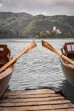 Close up view on beautiful wooden flat rowing boats with oars on lake bled, slovenia, go green concept. Close up view on beautiful wooden flat rowing boats with stock photography