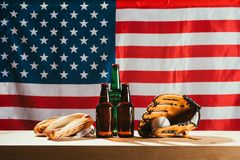 Close-up view of beer bottles, hot dogs, leather glove and baseball ball on wooden table with us. Flag behind royalty free stock photo