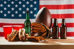 Close-up view of beer with hot dogs and sport equipment with us flag. Behind royalty free stock photography