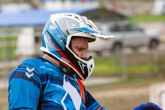 Close up view biker`s face in helmet. Closeup portrait of a man in motorcycle helmet. Park in the background royalty free stock photography