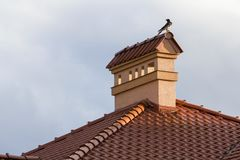 Close-up view of bird sitting on top of high plastered chimney o. F new big spacious modern house with shingled red roof against bright blue sky background royalty free stock image