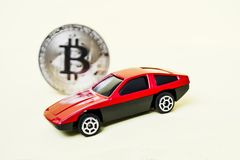 Close-up view of bitcoin and red car. royalty free stock image