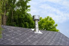 Close up view on bitumen asphalt roofing shingles and stainless steel chimney pipe. Close up view on bitumen asphalt roofing shingles and stainless steel royalty free stock photography
