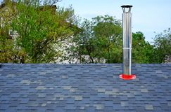 Close up view on bitumen asphalt roofing shingles and stainless steel chimney pipe. Individual heating system.  stock photo