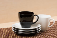 Close up view of black tea cup on the stack of the white and black plates near white tea cup on tablemat. Royalty Free Stock Image
