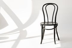 Close up view of black wooden chair on grey backdrop. With shadows stock images