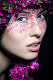 Close up view of blue-eyed girl with flowers Royalty Free Stock Image