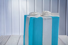 Close up view on blue gift box with white ribbon on wooden board Stock Images