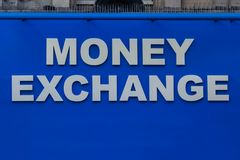 Close up view of blue light Money Exchange sign with spikes on top royalty free stock photos