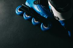 Close up view of blue roller skates inline skate or rollerblade on dark tinted grunge backgroung Royalty Free Stock Photography