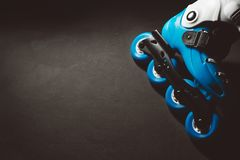 Close up view of blue roller skates inline skate or rollerblade on dark tinted grunge backgroung. Street culture, sports equipment Stock Photos