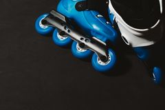 Close up view of blue roller skates inline skate or rollerblading on dark tinted grunge backgroung. Street culture, sports equipment Stock Photography