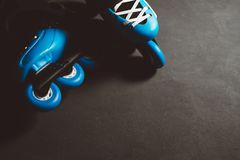 Close up view of blue roller skates inline skate or rollerblading on dark tinted grunge backgroung. Street culture, sports equipment Stock Image