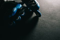 Close up view of blue roller skates inline skate or rollerblading on dark tinted grunge backgroung Stock Photo