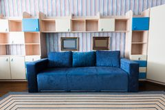 Close up view of blue sofa and wooden closet in living. Room royalty free stock images