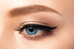 Close up view of blue woman eye with beautiful makeup. Close up view of blue woman eye with beautiful golden shades and black eyeliner makeup. Classic make up Stock Photography