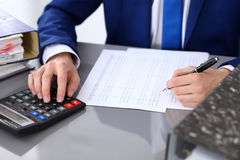Close up view of bookkeeper or financial inspector hands making report, calculating or checking balance. Internal Royalty Free Stock Image
