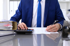 Close up view of bookkeeper or financial inspector hands making report, calculating or checking balance. Internal Royalty Free Stock Images