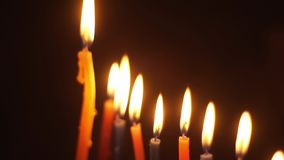 Close-up view of a bottom-up on candles in Hanukkah. Spinning on a black background stock footage