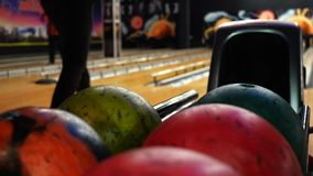 Close-up view of bowling player hand taking colorful ball from bowl lift. Media. People playing bowling - the bowling
