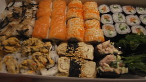 Close up view of a box full of sushi. The waiter delivers the box of sushi stock video footage