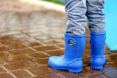 Close up view of boy in blue gumboots standing Royalty Free Stock Image