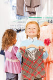 Close-up view of boy with hanger and girl behind Stock Image