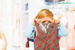 Close-up view of boy hiding behind hanger and vest Stock Images