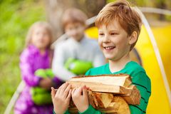 Close-up view of boy holding the wood for bonfire. With other kids and yellow tent during camping Royalty Free Stock Image