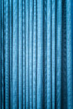 Blue curtain in folds. Textured background. Close-up view of bright blue curtain in thin and thick vertical folds made of dense fabric. Textured abstract Stock Images
