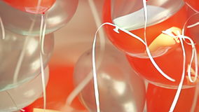 Close-up view of bright orange, silver and white balloons filled up with helium at children's birthday party