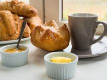 A brioche, French bun , croissants, with butter, jam and a cup o. Close up view of a brioche, French bun , croissants, with butter, jam and a cup of coffee in stock photos