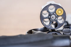 Close up view of bullet and handgun. Shallow depth of field. Focus on a bullet. Vertical view Royalty Free Stock Photo