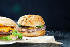 Close up view on burger with meat, sauce and greens on craft paper on a dark background. royalty free stock images