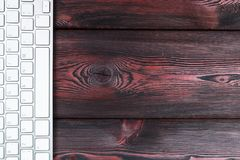 Close up view of a business workplace with wireless computer keyboard, keys on old red dark natural wooden table background. Royalty Free Stock Image