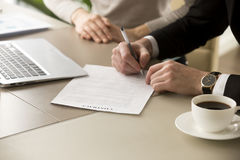 Close up view of businessman hand puts signature, signing contra. Businessman in suit puts signature on contract at business meeting after negotiations with Royalty Free Stock Photo